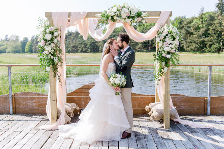 the bride and groom kissing in light and airy photograph