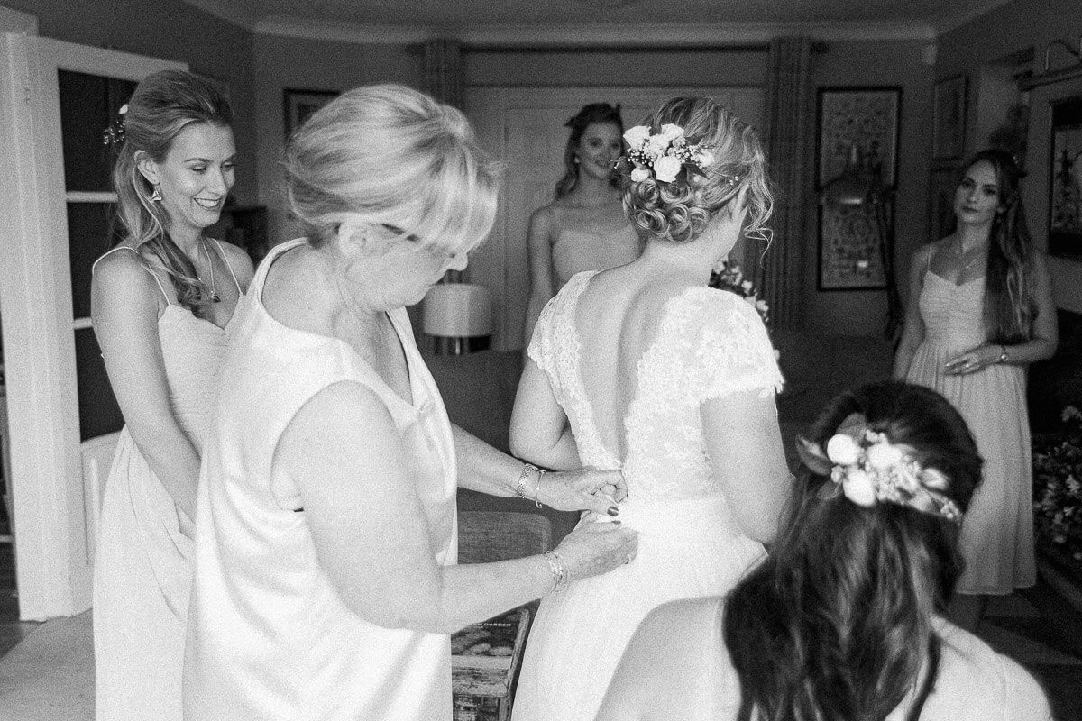 mother and bridesmaids helping the bride getting ready