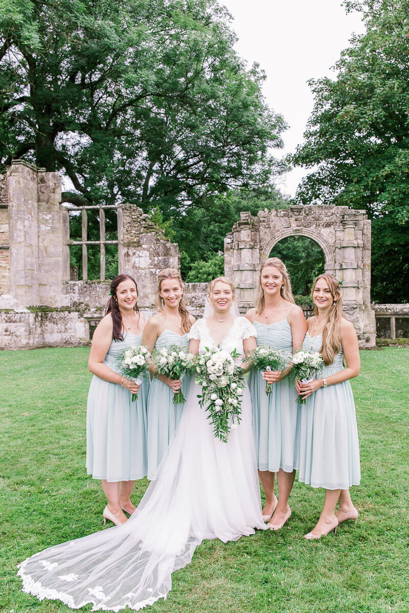 bride and her bridesmaids together in the gardens at slaugham place in sussex