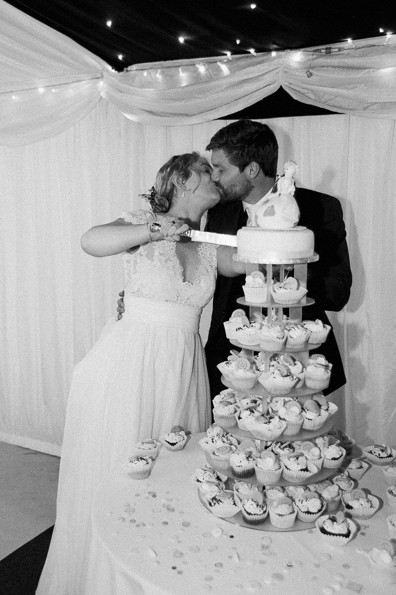 wedding cake cutting photograph in black and white