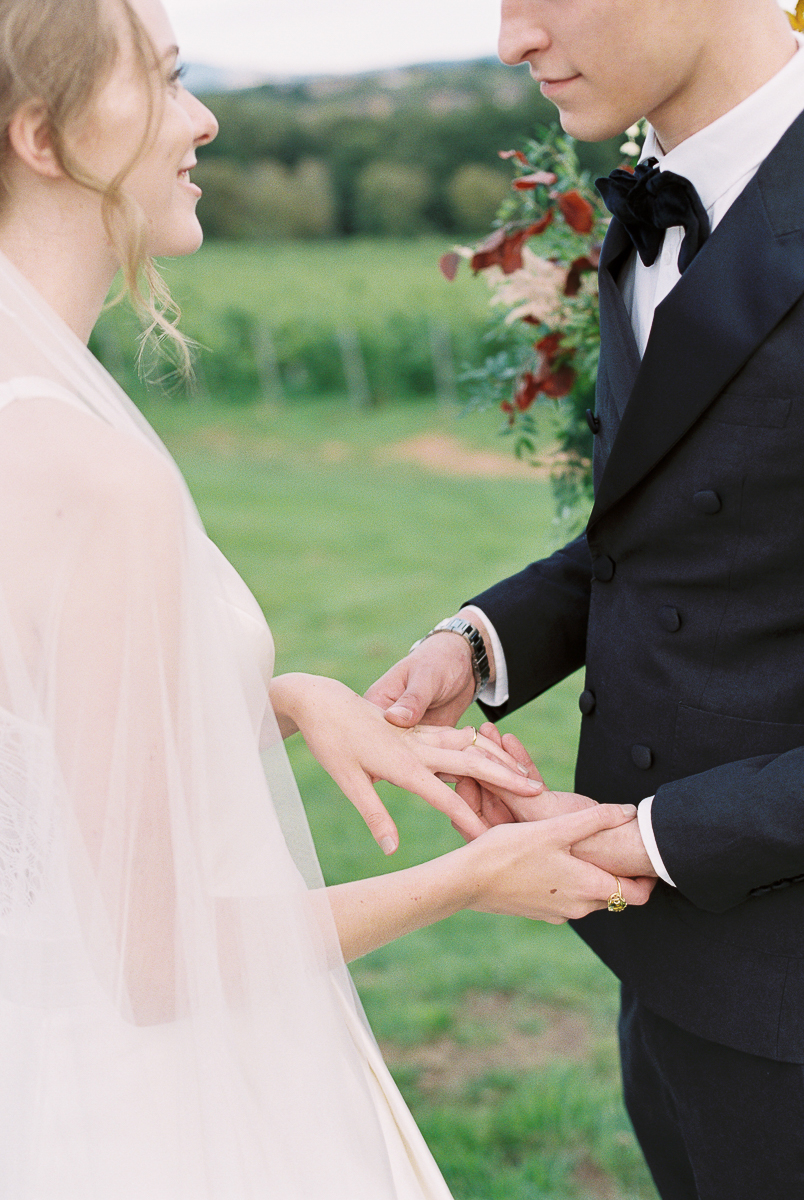 bride and groom exchaning with rings