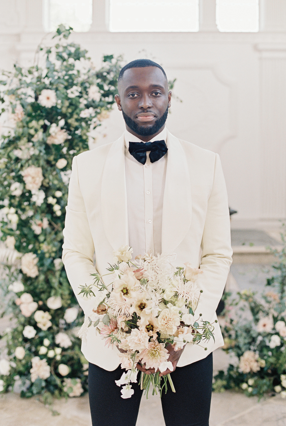 the groom holding brides bouquet