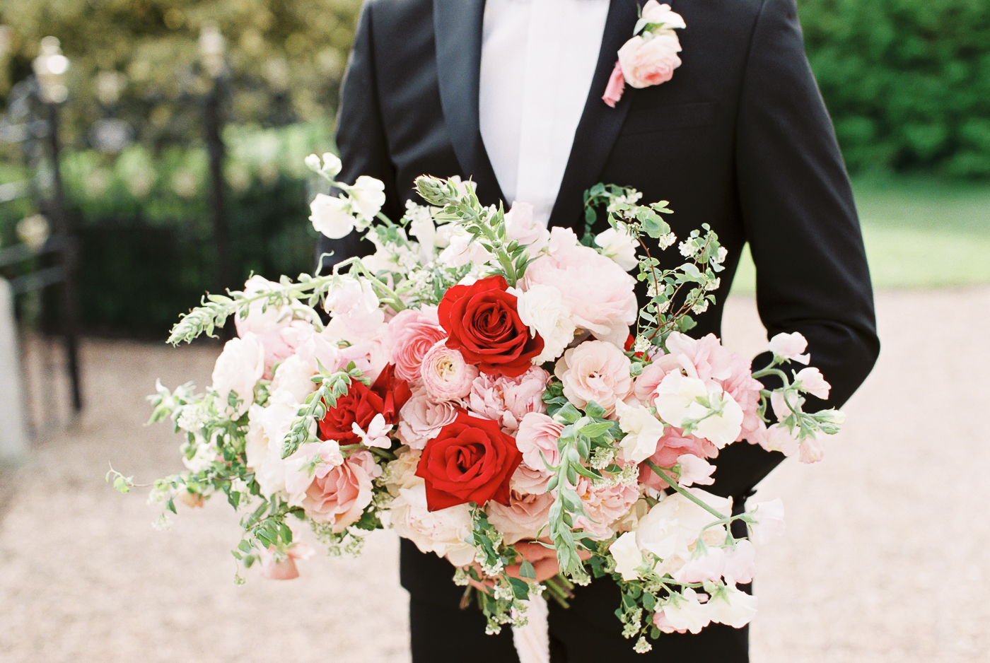 the groom holding brides flower bouquet